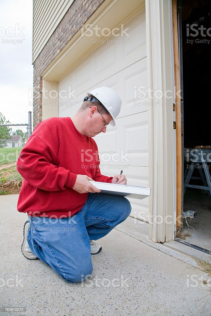 Man kneeling inspecting a home royalty-free stock photo