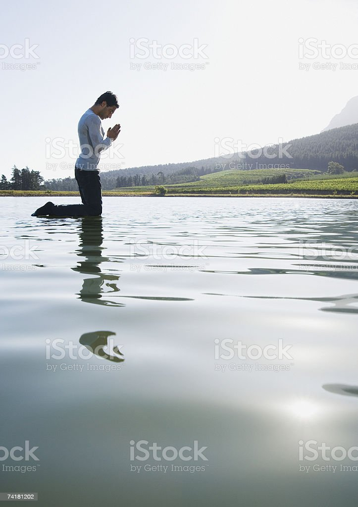 Man kneeling on water praying stock photo