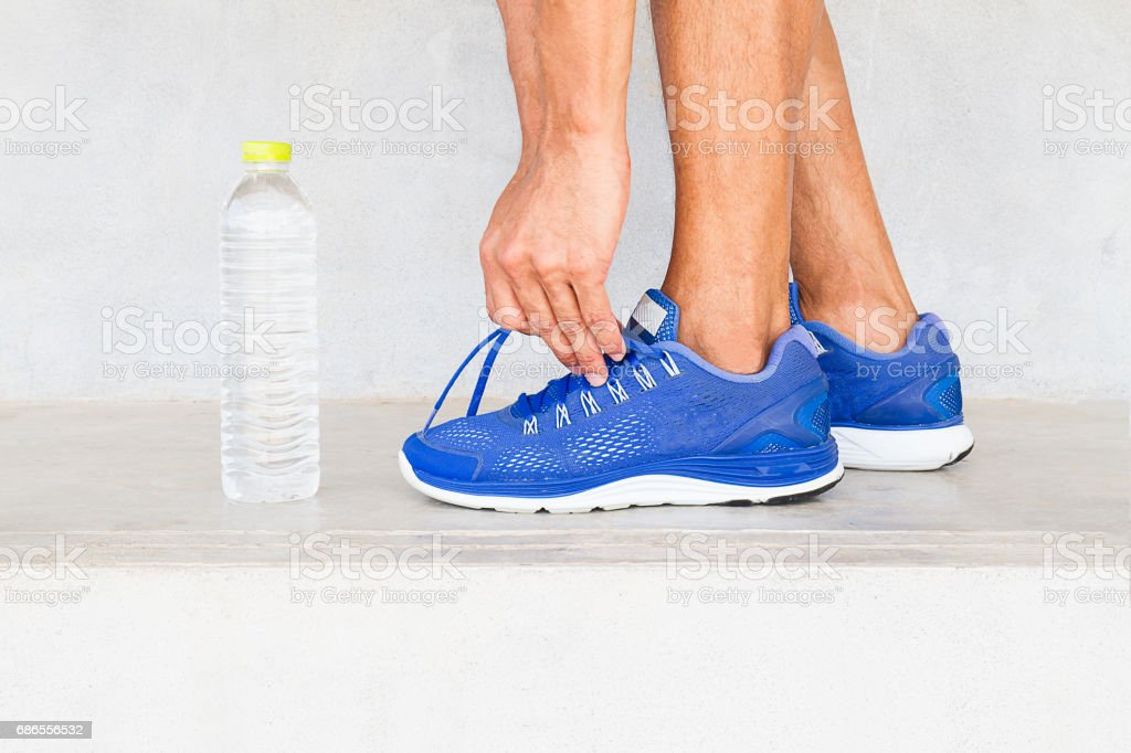 Man lacing sport shoes with water bottle, sport exercise concept foto stock royalty-free