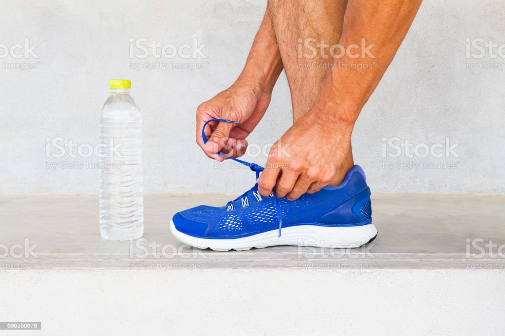 Man lacing sport shoes with water bottle, sport exercise concept foto de stock libre de derechos
