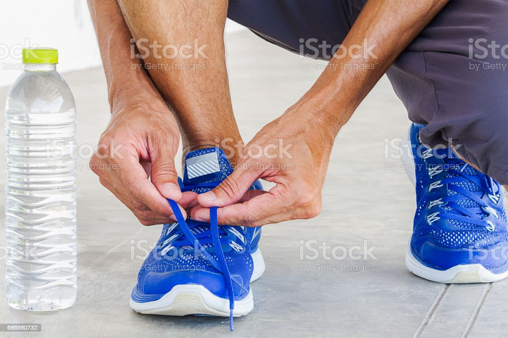 Man lacing sport shoes with water bottle, sport exercise concept royalty-free stock photo