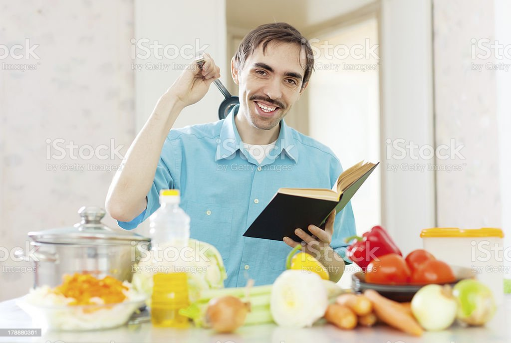 man ladle pan and cookbook in  kitchen royalty-free stock photo