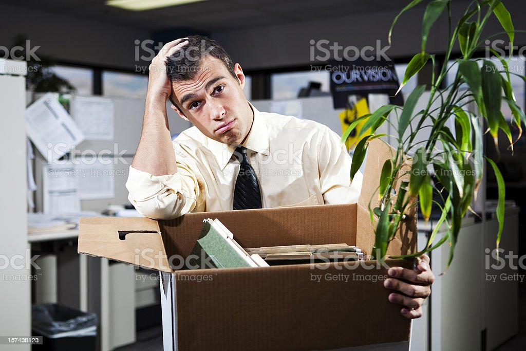 Man laid off and packing his things at work stock photo