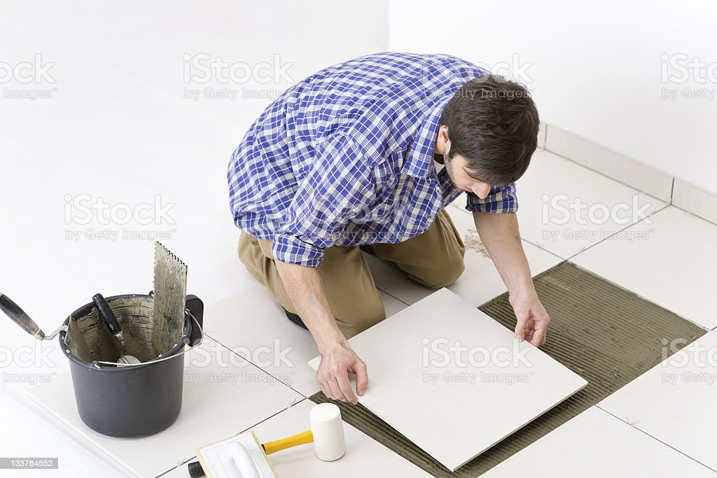 Man laying a tile on floor while doing some home improvement stock photo