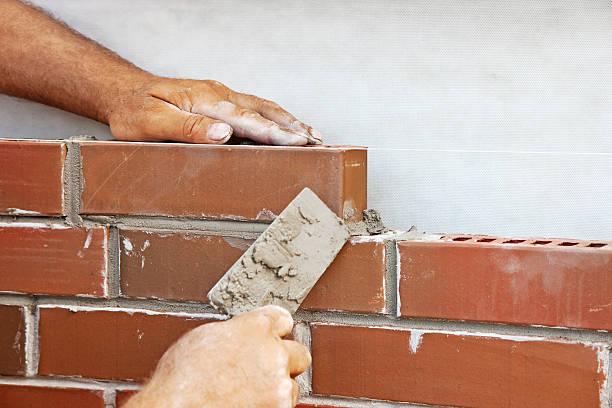 Man laying bricks on a new house stock photo