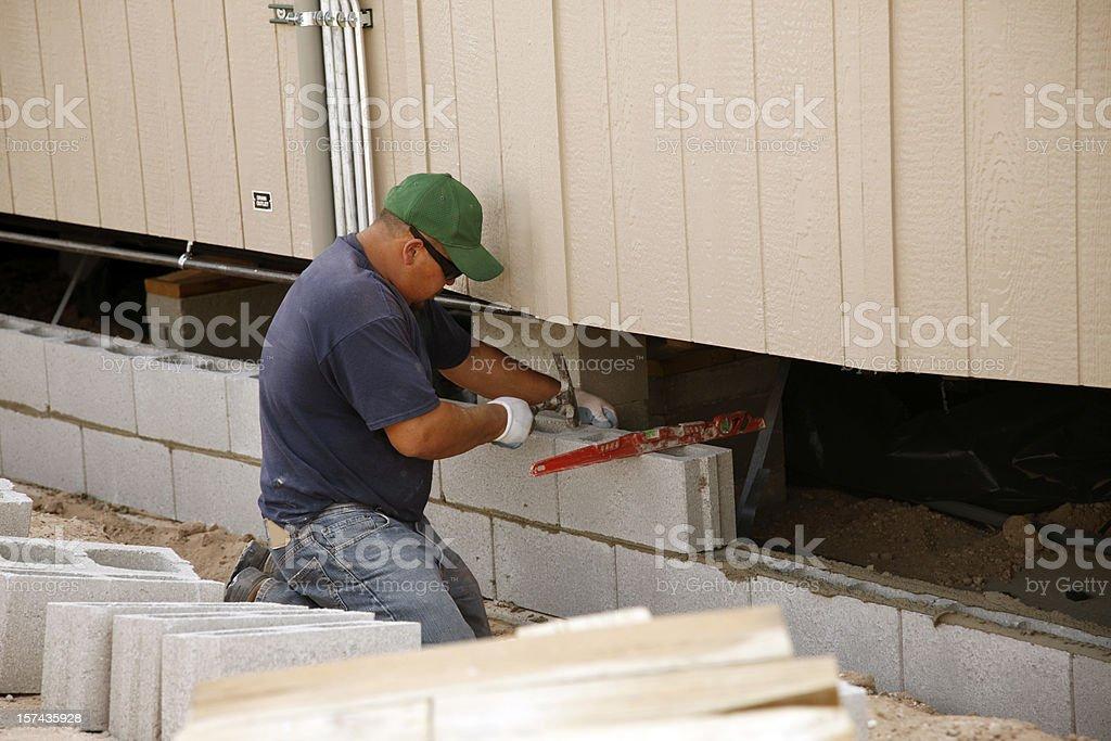 Man Laying Concrete Block Skirting stock photo