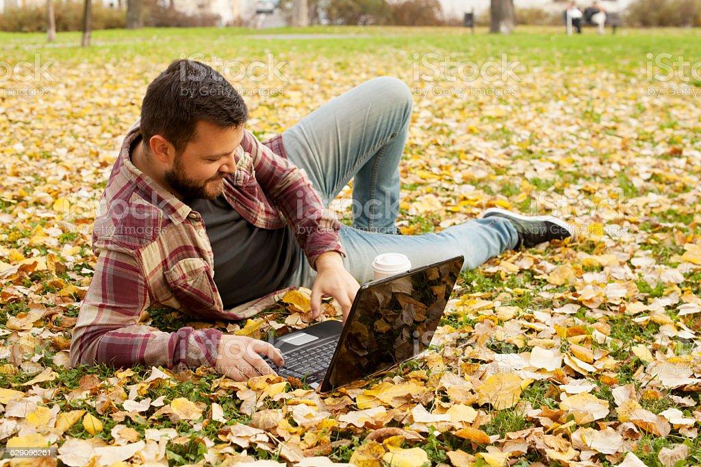Mann Festlegung im Herbst Blätter mit Laptop-Computer – Foto