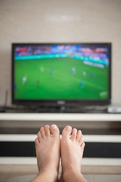 man laying down on a sofa  watching soccer match - fußball themenzimmer stock-fotos und bilder
