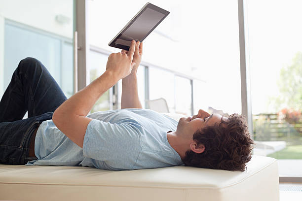 Man laying down using digital tablet stock photo