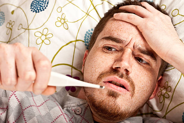 A man laying in bed measuring his fever stock photo