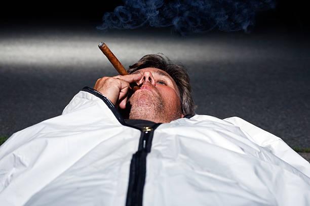 Man laying in body bag smoking a cigar stock photo