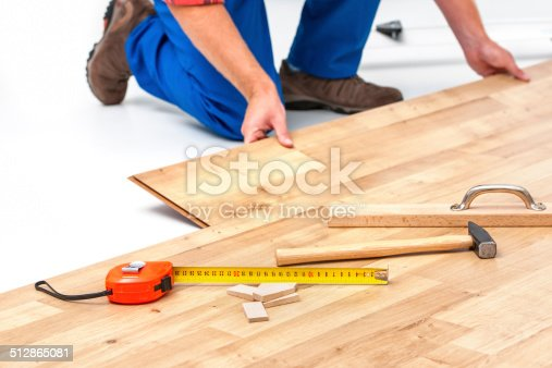 istock Man laying laminate flooring 512865081