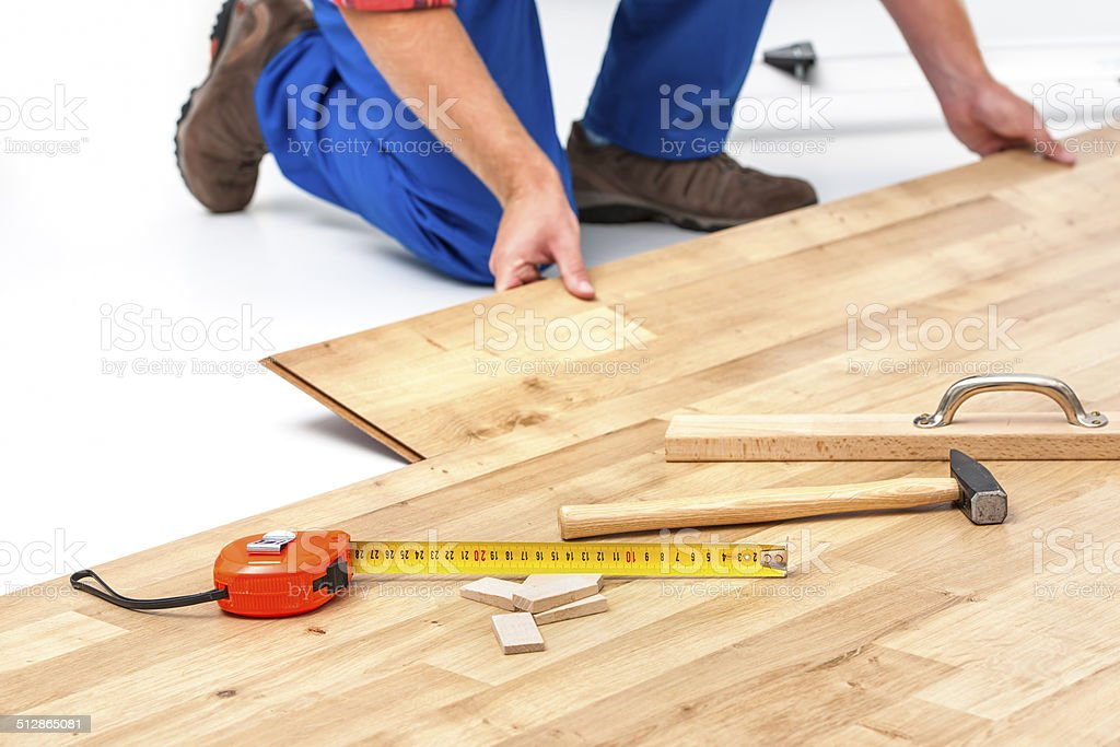 Man laying laminate flooring stock photo