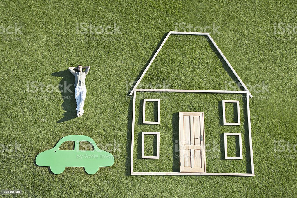 Man laying on grass next to outline of house and car stock photo