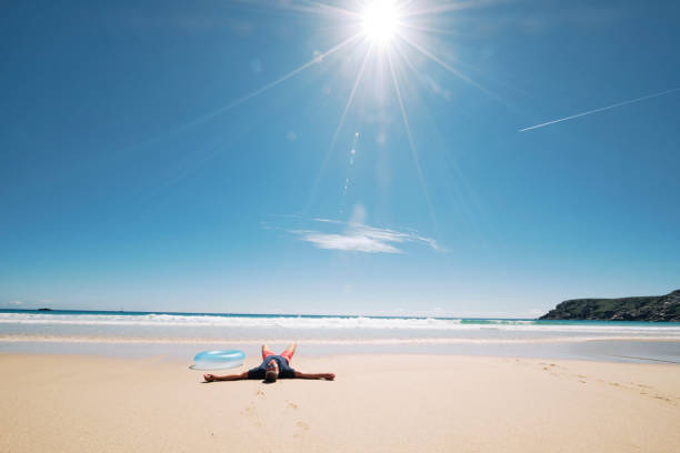 man laying on his back on the sand of the pristine pedn vounder beach, cornwall. - rubber ring stock photos and pictures