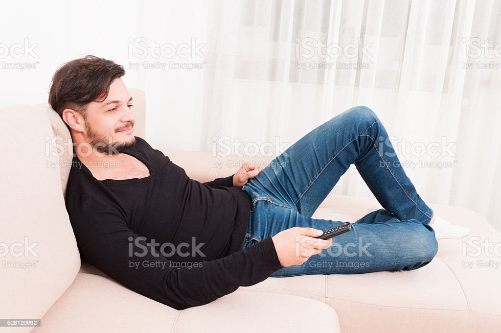 Man laying on sofa holding remote control and smiling stock photo