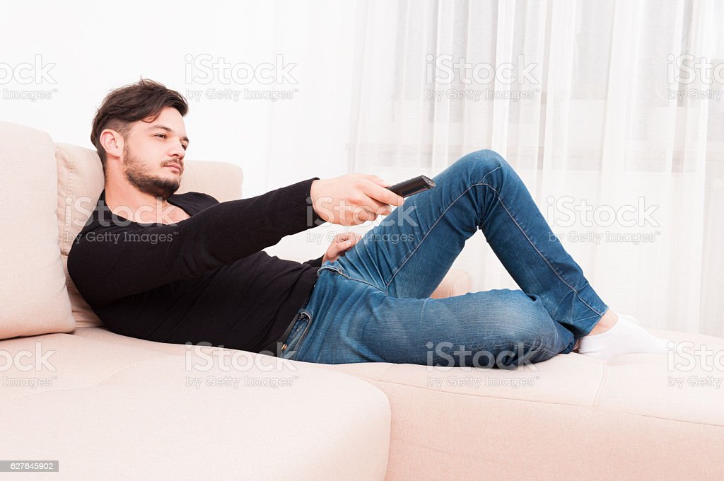 Man laying on sofa holding remote control stock photo