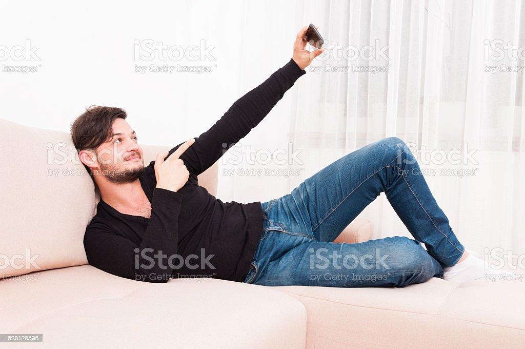 Man laying on sofa holding smartphone taking selfie stock photo
