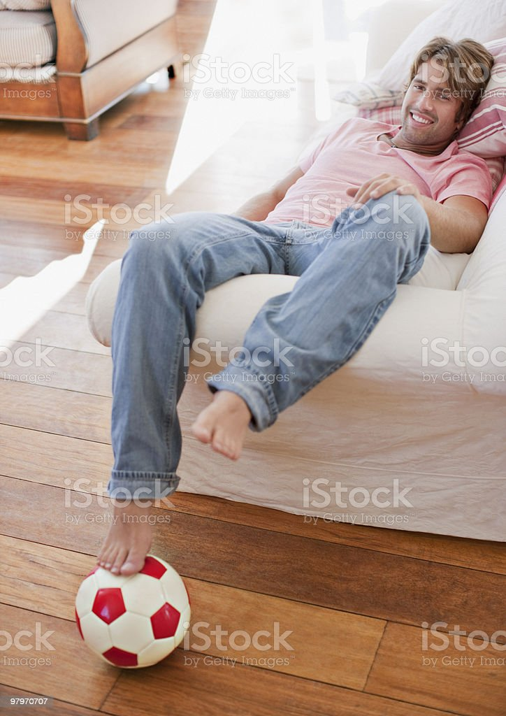 Man laying on sofa with foot on soccer ball royalty-free stock photo