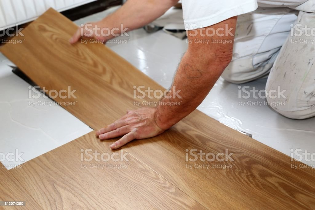 Man laying PVC-floor stock photo