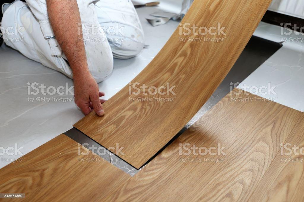 Man laying PVC-floor stock photo