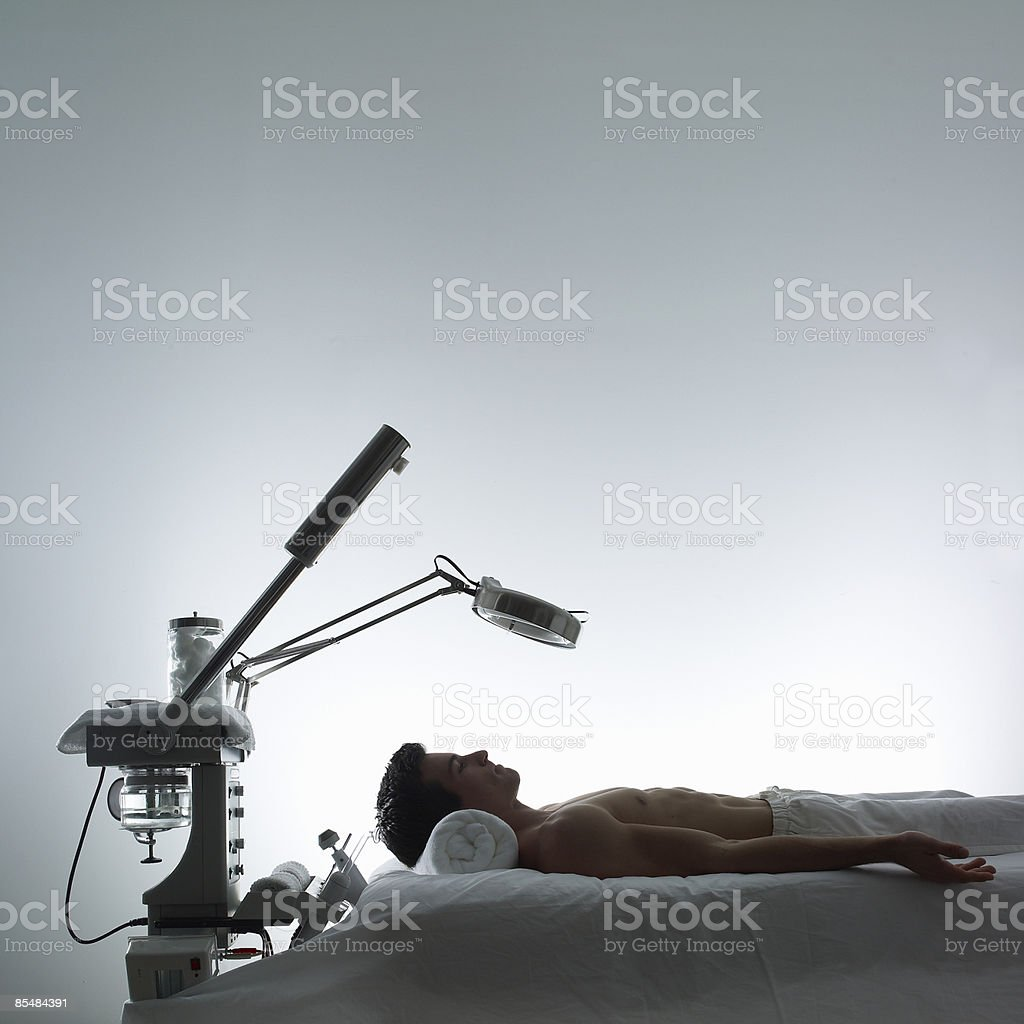 Man lays on table with microdermabrasion machines royalty-free stock photo