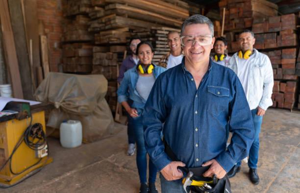 Mann führt eine Gruppe von Arbeitern in einem Möbelhaus – Foto