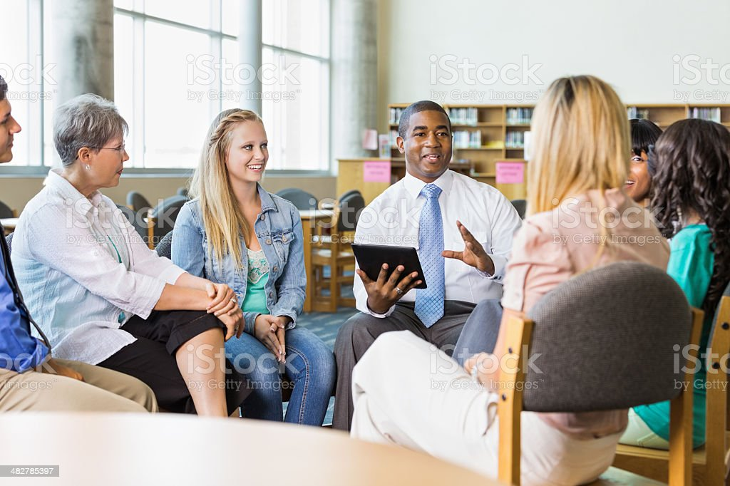 Man leading discussion group of adults and teens stock photo