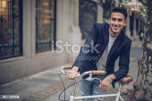 Handsome young man leading his bike