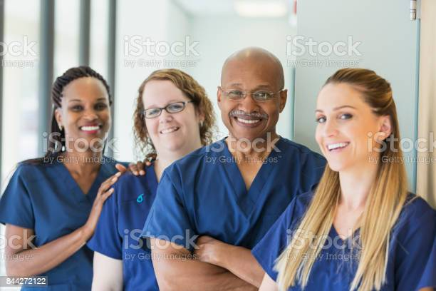 A team of four multi-ethnic medical professionals standing in a corridor, wearing blue scrubs, smiling at the camera. The focus is on the African-American senior man, in his 60s.