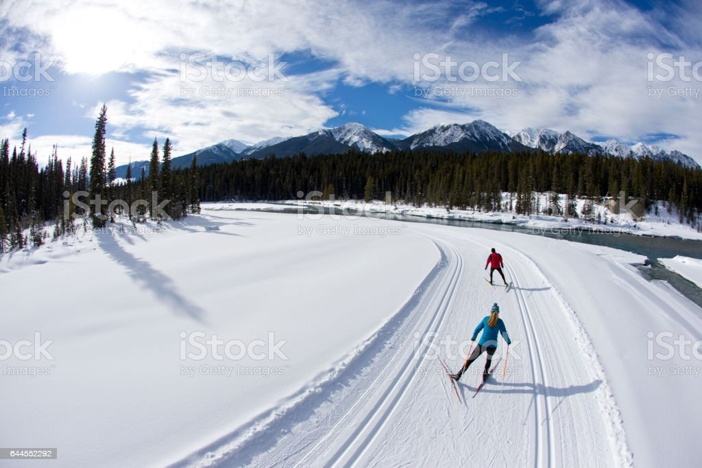 A man leads a woman on a cross-country skate ski next to a river in British Columbia, Canada. stock photo