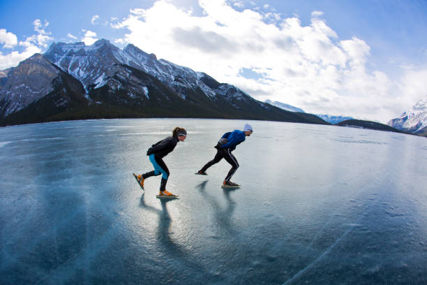 a man leads a woman on a winter speed skating adventure on lake minnewanka in banff national park, alberta, canada. - banff national park stock photos and pictures