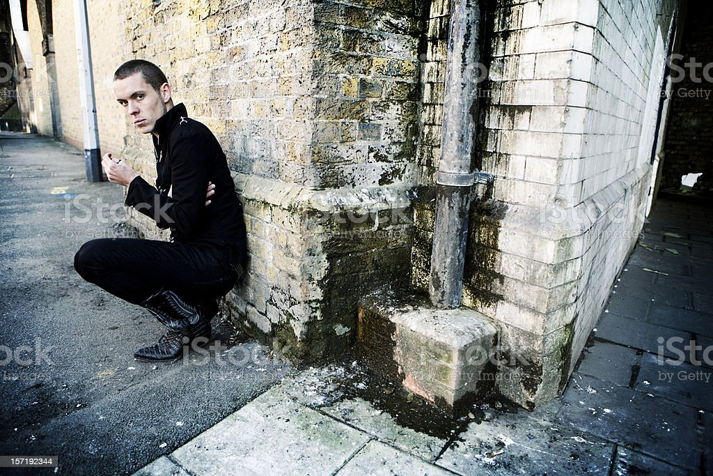 A man leaning against an exterior brick wall stock photo