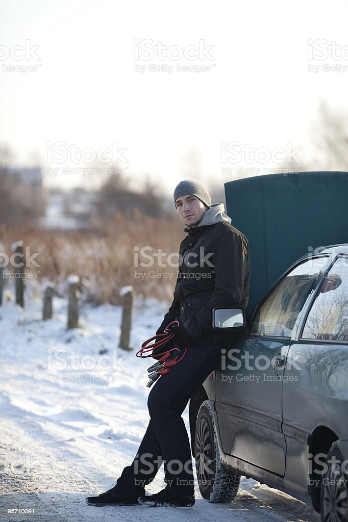 Man leaning against broken car in snow, holding jump cable royalty-free stock photo