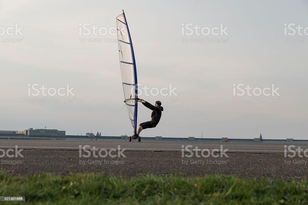 man leaning back on windskateboard at tempelhof airport stock photo