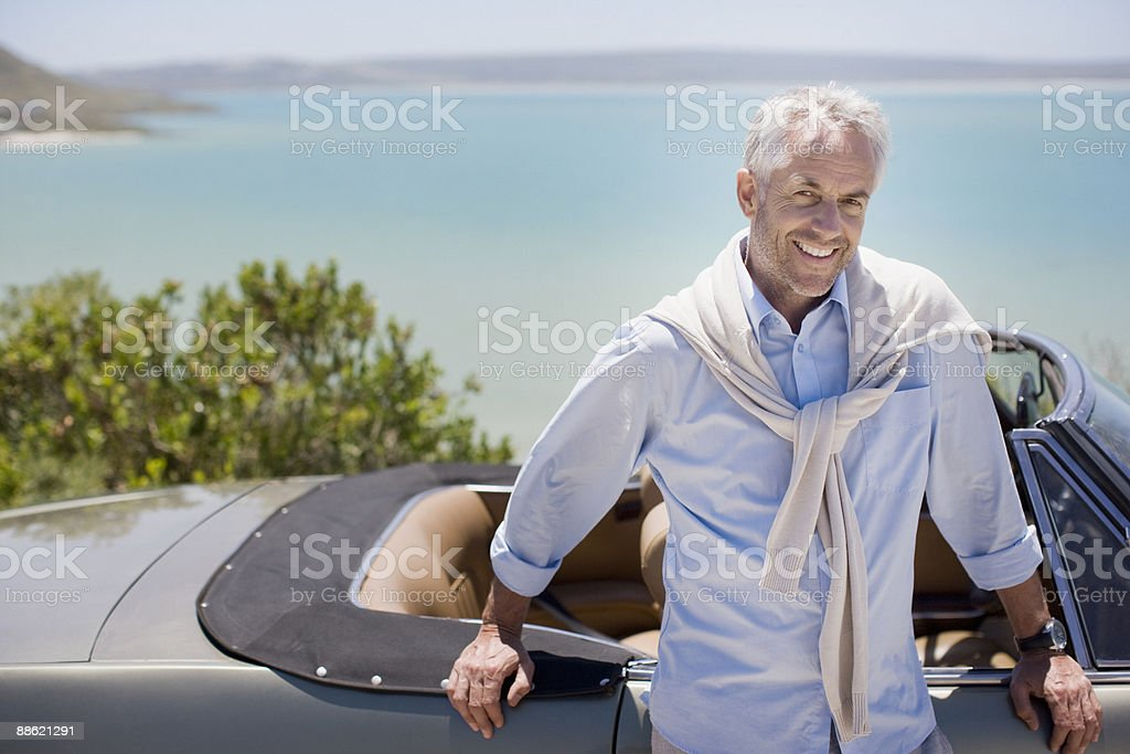 Man leaning on convertible at waterfront royalty-free stock photo