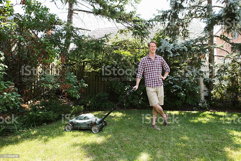 Man leaning on lawnmower stock photo