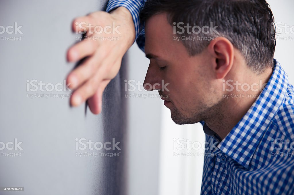 Man leaning on the wall stock photo
