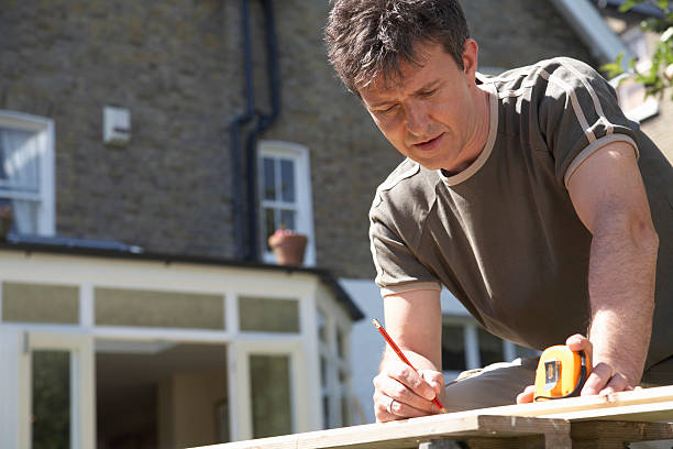 Man leaning on workbench in garden, using pencil and tape measure stock photo