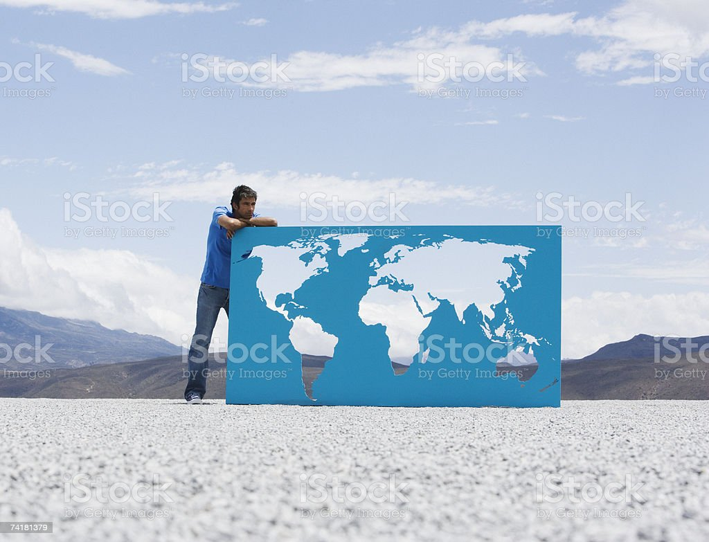 Man leaning on world map outdoors royalty-free stock photo