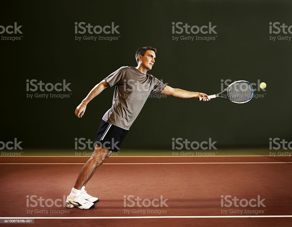Man leaning to hit tennis ball 免版稅 stock photo