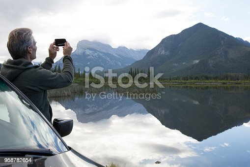 527894422 istock photo Man leans against car at takes photo of mountain reflected in lake 958782654