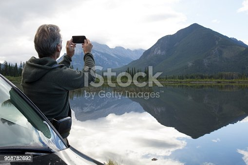 527894422 istock photo Man leans against car at takes photo of mountain reflected in lake 958782692
