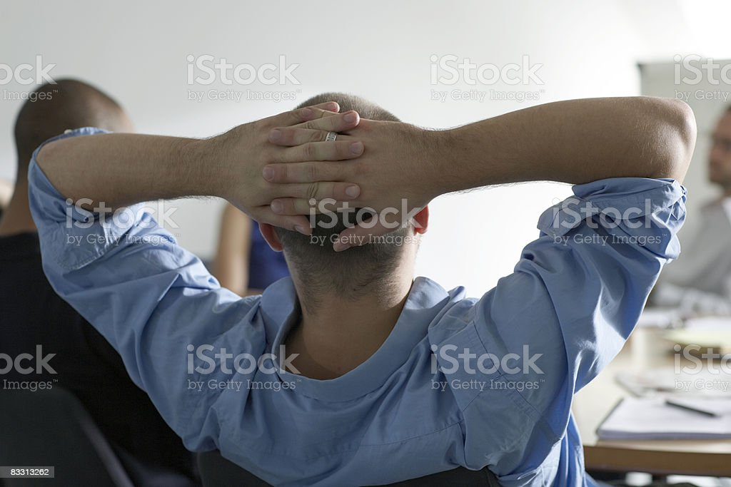 man leans back in office meeting royalty free stockfoto