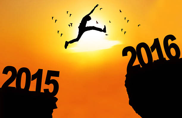 Man leap over cliff with numbers 2015 and 2016 stock photo