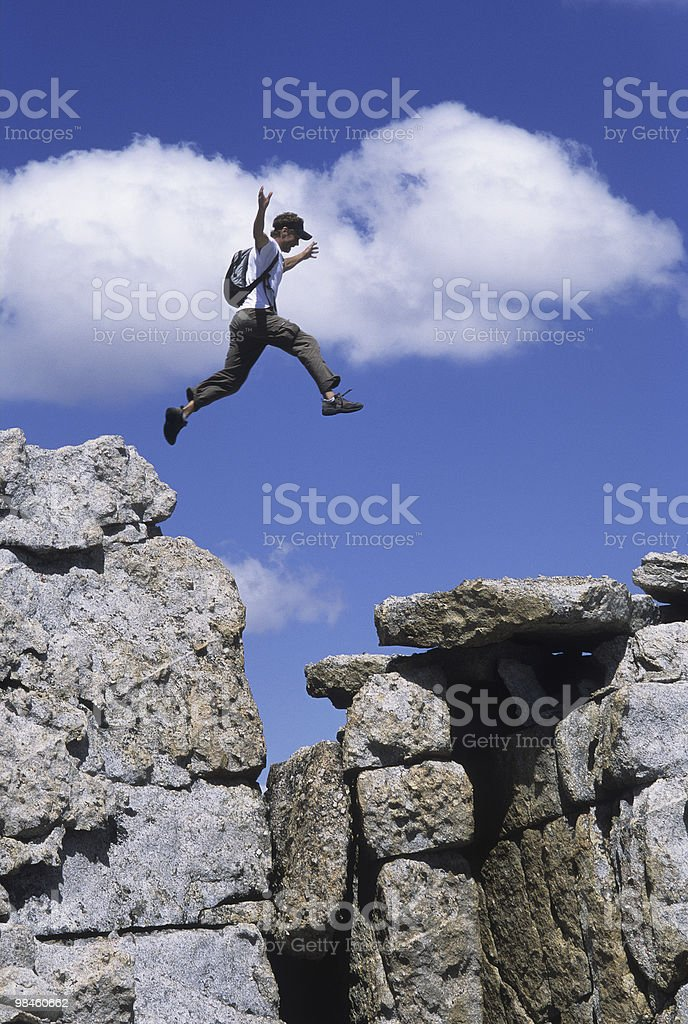 Man Leaping a gap of rocks royalty-free stock photo