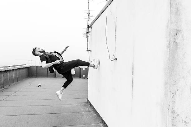 mann springen gegen die wand - parkour stock-fotos und bilder