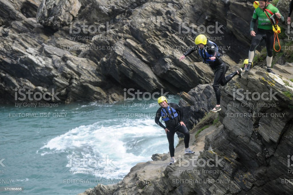 Man leaping from cliff into the sea at Newquay, Cornwall. royalty-free stock photo