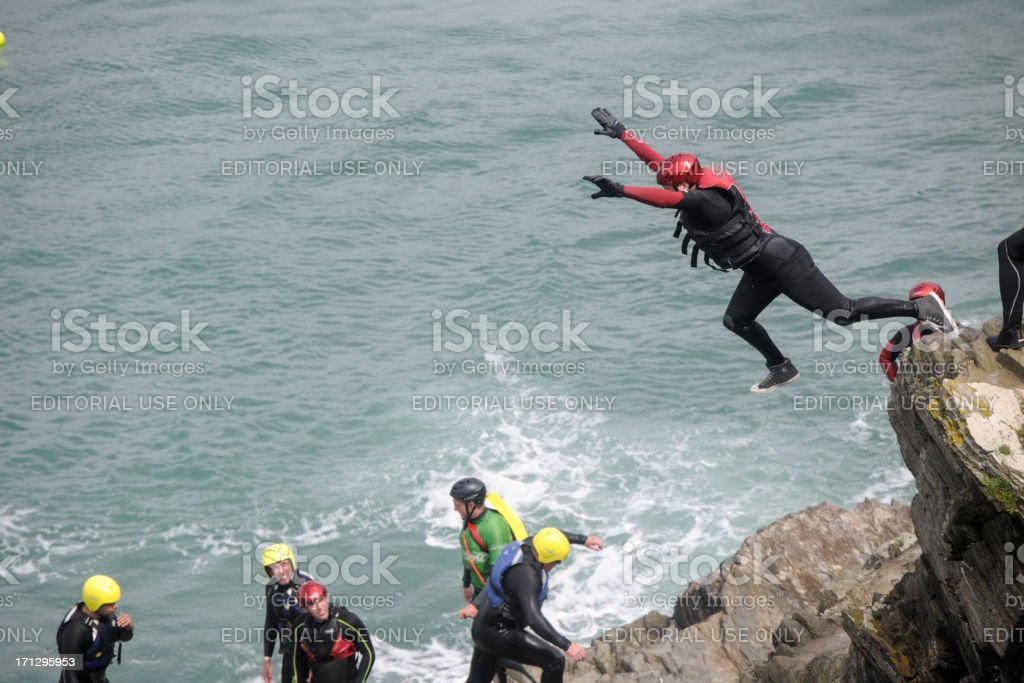 Man leaping from cliff into the sea at Newquay, Cornwall. stock photo