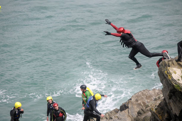 man leaping from cliff into the sea at newquay, cornwall. - cornwall stock pictures, royalty-free photos & images